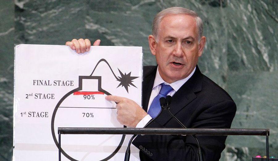 """Le Premier ministre israélien Benjamin Netanyahu a réclamé jeudi aux Nations unies qu'une """"ligne rouge"""" soit fixée à l'Iran pour l'empêcher de se doter de l'arme nucléaire. Et le chef du gouvernement de l'Etat hébreux de brandir le dessin d'une bombe prête à exploser et de tracer une ligne rouge. """"Une ligne rouge devrait être tracée juste ici, avant que l'Iran ne finalise la deuxième étape de son enrichissement nucléaire nécessaire à la fabrication d'une bombe, avant que l'Iran n'en soit qu'à quelques mois ou quelques semaines d'avoir amassé suffisamment d'uranium enrichi pour fabriquer une arme nucléaire"""", a-t-il commenté en tirant un trait rouge à 90%, selon son dessin, du processus de fabrication de la bombe."""
