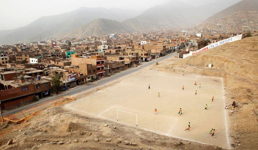 Des enfants des bidonvilles de Lima, au Pérou, jouent au football.
