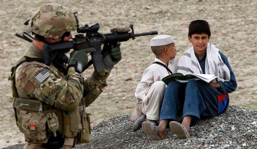 Deux enfants afghans regardent un soldat américain, alors qu'il a l'œil dans le viseur de son arme.