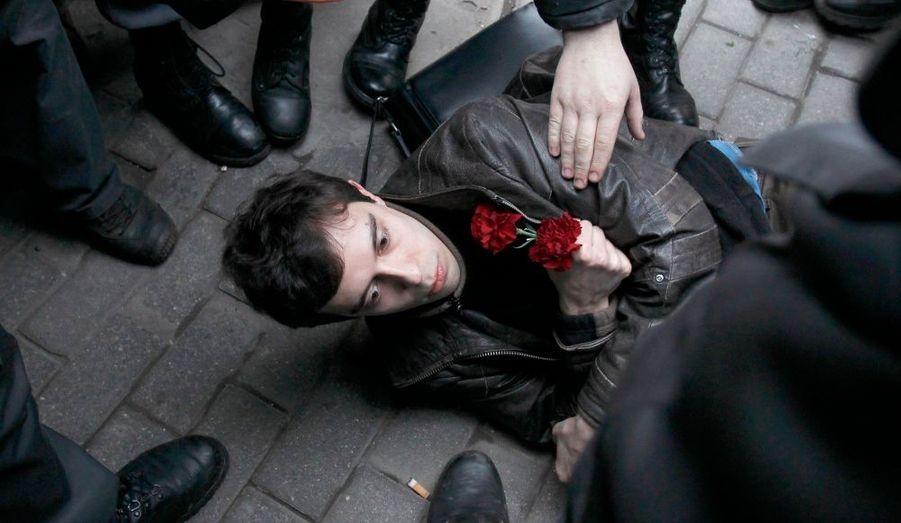 """La police russe arrête un partisan de l'opposition lors d'un rassemblement de protestation dans le centre de Moscou, le 31 Mars 2010. Les partisans de différents partis d'opposition se sont réunis pour pour défendre l'article 31 de la Constitution de la Fédération de Russie. Un article qui stipule que """"les citoyens de la Fédération de Russie ont le droit de se réunir pacifiquement, sans armes, et à tenir des réunions, des rassemblements, des manifestations, des marches et des piquets""""."""