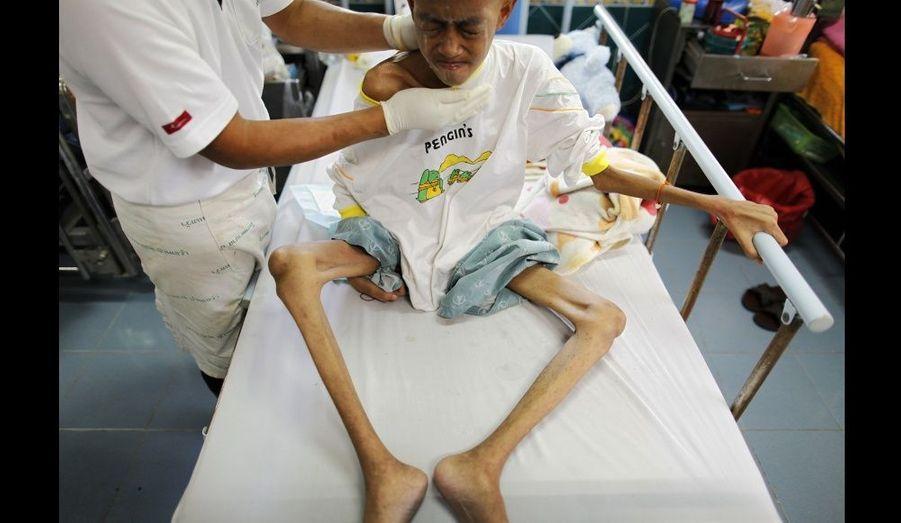 En phase terminale, ce jeune Thaïlandais atteint du virus du SIDA reçoit un traitement dans l'hospice du temple bouddhiste de Nampu. La Thaïlande a été félicitée pour sa prise en charge des malades et ses efforts de prévention. Selon l'ONUSIDA, le nombre de nouvelles infections est passé de 140 000 par an en 1991, à 18 000 en 2005.