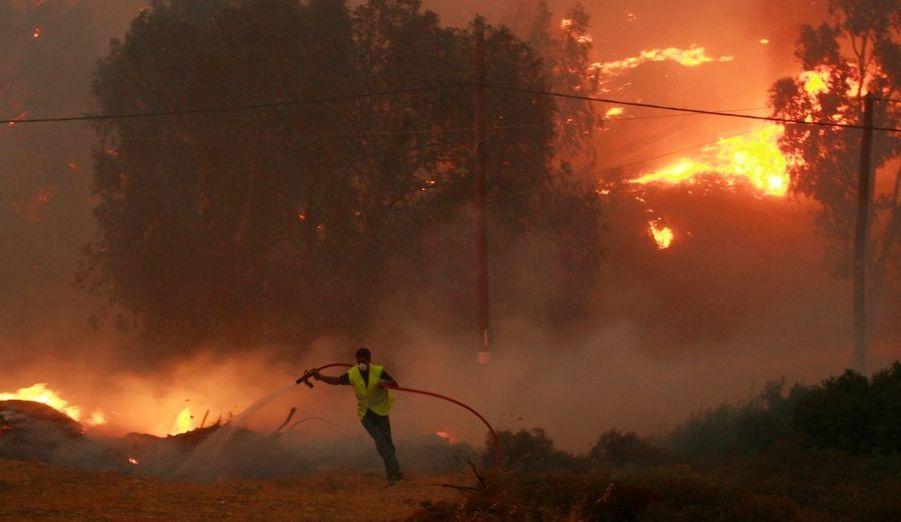 Un pompier volontaire combat les flammes dans la nuit de dimanche à lundi dans le quartier de Pallini, situé à moins de 30 km d'Athènes.