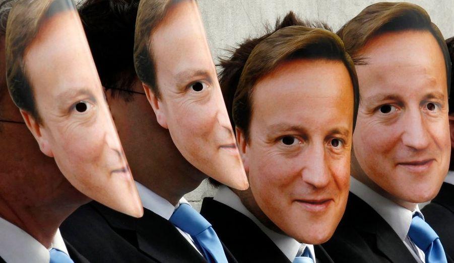 Des manifestants anglais ont enfilé des masques à l'effigie du Premier ministre britannique David Cameron, pour protester contre la vente de viande de vache clonée dans les rayons des supermarchés britanniques, hier à Londres.