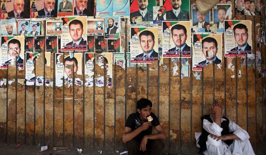 Deux hommes postés au pied d'un mur orné d'affiches des différents candidats à la présidentielle à Kaboul (Afghanistan). Les élections présidentielles se tiendront le mois prochain.