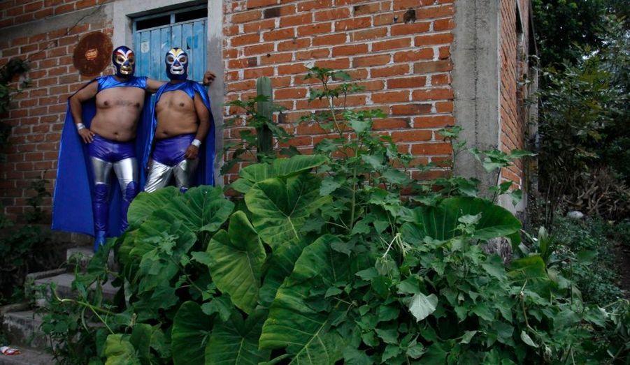 Deux hommes, habillés en catcheurs, se tiennent contre une maison de Zacualpan de Amilpas, au Mexique, à l'occasion des festivités célébrant l'archange Saint Michel.