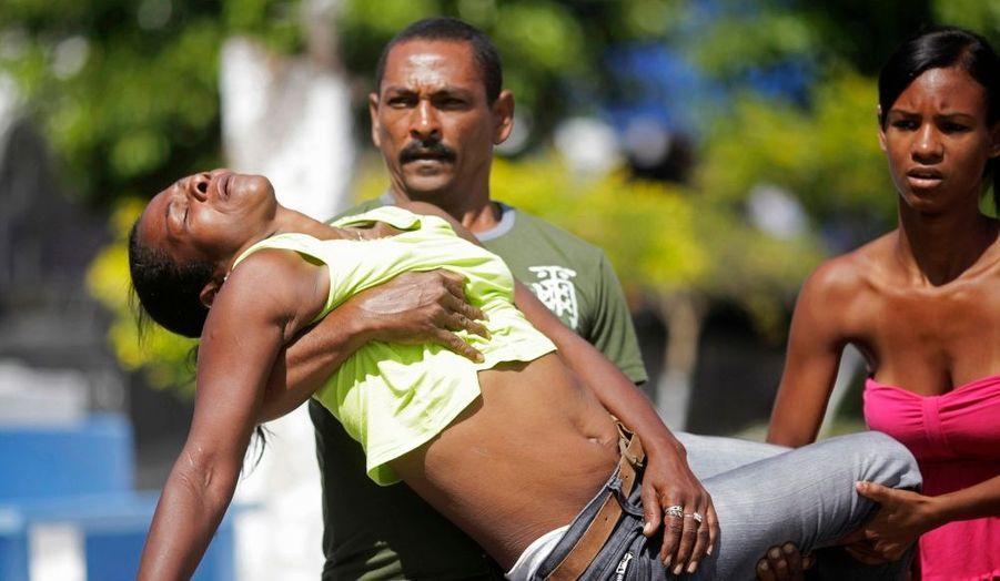 La mère d'une victime de la fusillade de Rio de Janeiro, évacuée d'un cimetière après avoir perdu connaissance alors qu'elle assistait aux funérailles de son enfant. Jeudi, Wellington Menezes, un jeune homme perturbé de 23 ans a fait irruption dans une école de la capitale et ouvert le feu, tuant 12 élèves et faisant 11 blessés.