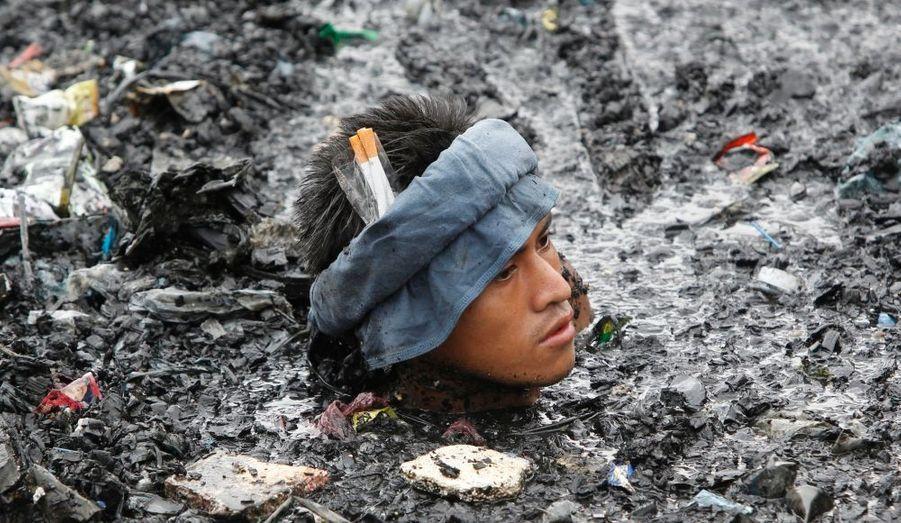Un homme se débat dans les décombres de sa maison, à Malabon, aux Philippines. Près de 500 maisons ont été incendiés après l'explosion d'un réservoir de pétrole. Aucune victime n'est à déplorer.