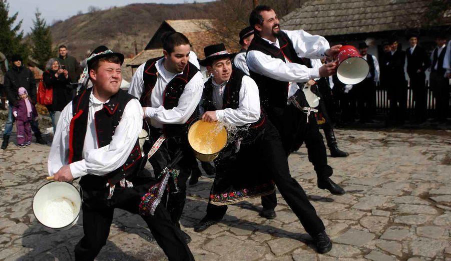 """A Holloko, village hongrois à une centaine de kilomètres de Budapest, les hommes jettent de l'eau sur une femme à l'occasion des célébrations de Pâques. """"L'arrosage des filles"""" est un rituel de fertilité traditionnel pour les habitants de ce village qui revêtent pour l'occasion des costumes régionaux."""