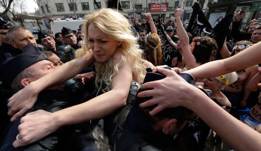 L'activiste ukrainienne Inna Shevchenko et d'autres membres du groupe Femen se battent avec les forces de police lors d'une manifestation à Paris, ce jeudi. L'évènement a été organisé en soutien à une activiste tunisienne qui a reçu des menaces après qu'elle a posté des photos seins nus sur Internet.