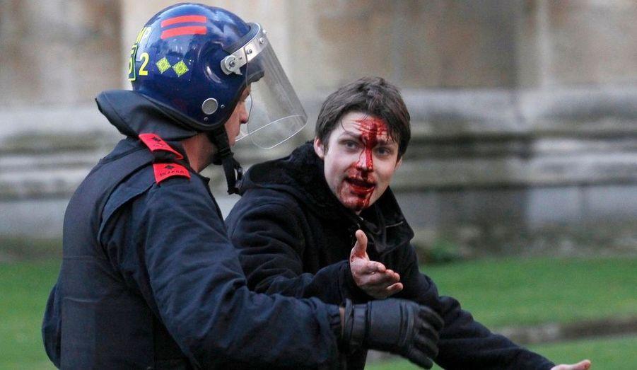 Un jeune homme blessé est emmené par un policier lors des manifestations estudiantines dans le centre de Londres. Le Parlement britannique a approuvé jeudi les plans d'augmentation des frais universitaires payés par les étudiants en dépit d'une rébellion des membres du gouvernement.