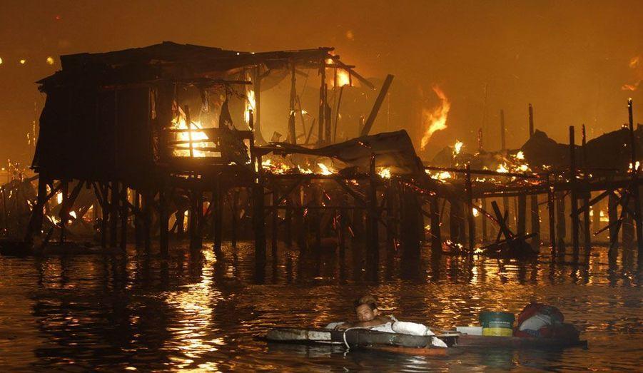 Un habitant du bidonville de la baie de Manille aux Philippines flotte sur les derniers restes de sa maison. Un terrible incendie a détruit au moins 1000 habitations, laissant ainsi 5000 familles sans abris.