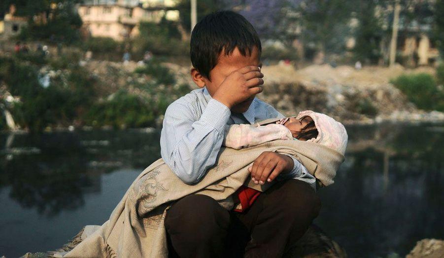 Un jeune garçon pleure, le couffin de sa soeur dans les bras, après des heurts qui ont opposé les habitants d'un quartier de Kathmandou, au Népal, aux forces de l'ordre. Le gouvernement a décidé d'employer la méthode forte pour déloger des squatters qui ont construit illégalement des maisons.