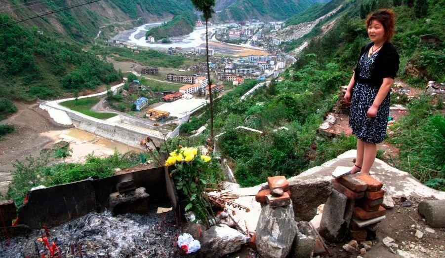 Une ancienne habitante de la ville montagneuse de Sichuan pleure sur la tombe de son enfant. Il y a trois ans, son petit de six ans périssait à l'école suite à un tremblement de terre de magnitude 8 sur l'échelle de Richter. Environ 87 000 personnes ont péri ou ont disparu.