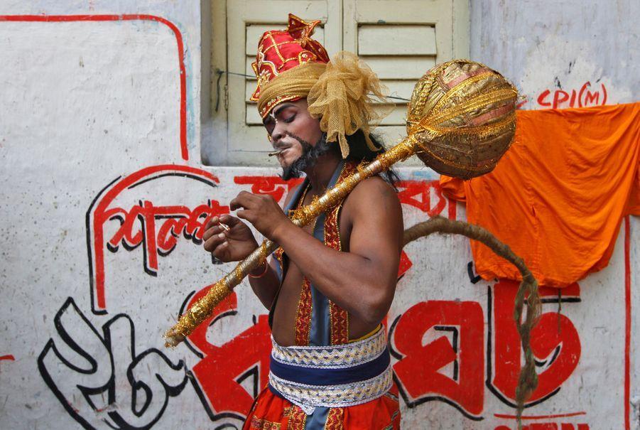 Un participant au festival Gajan, à Kolkata en Inde, se grille une cigarette lors d'une pause. Pendant un mois, les Hindous prient et chantent pour s'attirer les bonnes grâces des Dieux.