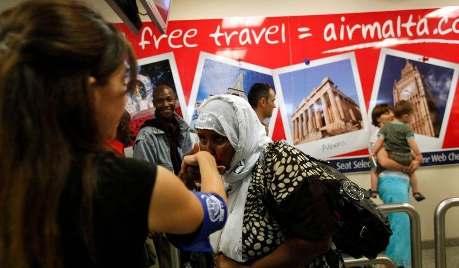Une immigrante embrasse la main d'une membre de l'Organisation internationale pour les migrations en arrivant à Paris. Eric Besson, ministre de l'Immigration, de l'Intégration, de l'Identité nationale et du Développement solidaire a accueilli jeudi à l'aéroport de Roissy Charles de Gaulle 892 réfugiés originaires de la corne de l'Afrique (Somalie, Erythrée, Soudan, Ethiopie, Sri Lanka, Côte d'Ivoire) auxquels Malte a accordé une protection internationale, dans le cadre de la décision du Conseil européen d'accueillir sur la base du volontariat des migrants s'étant vus octroyer une protection par l'archipel maltais. Ils seront hébergés dans des centres collectifs.