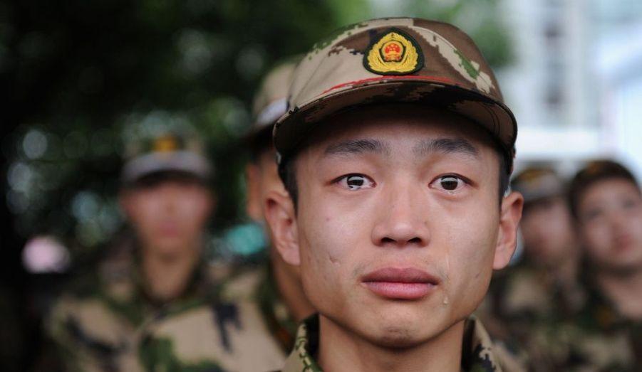 A une station de chemin de fer à Jiaxing, province du Zhejiang, une recrue de la police paramilitaire pleure avant de partir dans la région ouïgoure du Xinjiang pour commencer son service.
