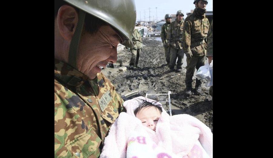 Un militaire tient dans ses bras un nourrisson de quatre mois, dans la ville d'Ishimaki.