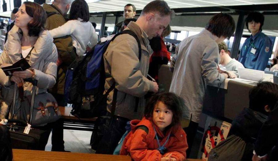 Des résidents français au Japon se préparent à l'enregistrement d'un vol spécial à destination de Paris, à l'aéroport de Narita.