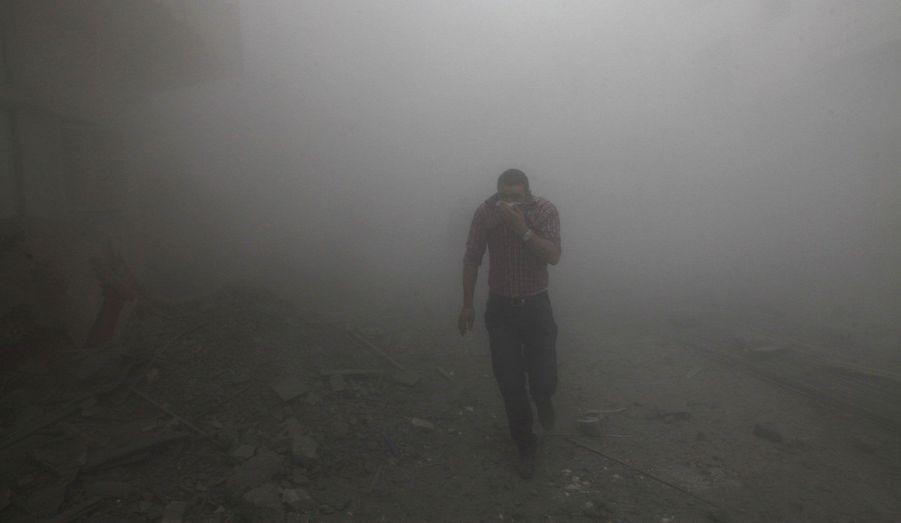 Un homme court et se couvre le visage lors de combats entre les forces rebelles et les forces loyales en Syrie.
