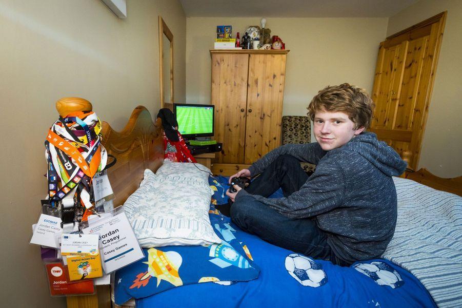 """Jordan Casey dans sa chambre à l'étage de la maison familiale de Waterford. C'est ici qu'il conçoit ses jeux sur ce Mac portable. Il garde, accrochés à son lit, les badges qu'il a porté dans la cinquantaine de conférences internationales auxquelles il a participé. Il passe aussi beaucoup de temps à jouer au foot sur sa console.<center><iframe width=""""560"""" height=""""315"""" src=""""https://www.youtube.com/embed/qQOfMtvr3-o"""" frameborder=""""0"""" allowfullscreen></iframe></center>"""