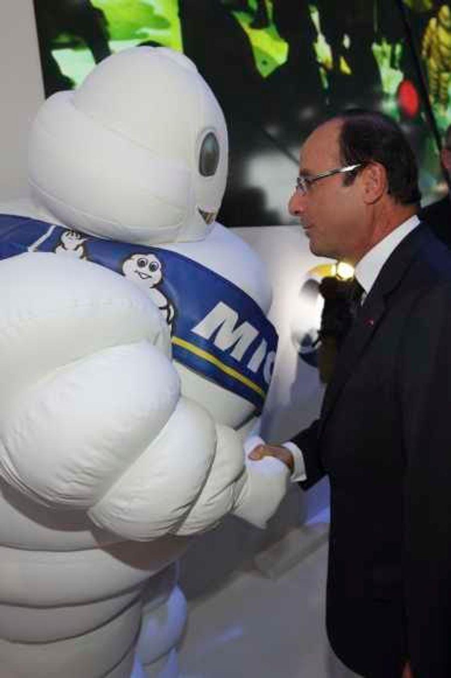 François Hollande serrant la main du bonhomme Michelin.