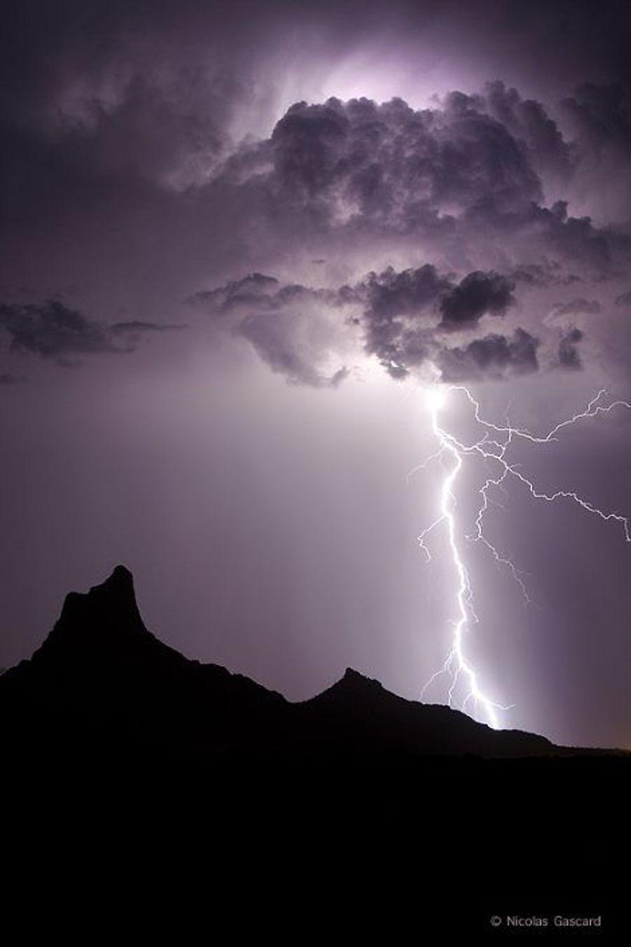 """Une violente illumination intranuageuse provoque un coup de foudre près du célèbre Picacho.A 33 ans, Nicolas Gascard, a consacré 18 ans de sa vie à traquer lafoudre. Il a parcouru plus de 400 000 kilomètres à travers le monde pour capturer le plus puissant et le plus rapide des phénomènes climatiques : le courant se propage à près de 100 000 km/s et la décharge peut atteindre 100 millions de volts. De cette passion est né un livre magnifique, «Foudre lumière et furie», paru le 17 novembre. Il nous confie l'origine de sa fascination pour l'attribut de Jupiter tonnant.«Enfant, en 1988, j'ai vu la foudre tomber sur le clocher du village et le coq de la girouette exploser.Quelques années plus tard, en 1993, j'ai assisté à une autretempêtequi s'est déchaînée sur la commune causant des dégâts considérables. Ces deux évènements ont forgé ma vocation. Je suis fasciné par cette puissance démentielle qui nous renvoie à la fragilité de la condition humaine. On se sent minuscule face à cette force. On ne peut rien contre la foudre qui frappe au tiers de la vitesse de la lumière. La photographie n'est finalement qu'un moyen d'assouvir ma première passion, la foudre. Je ne suis pas un chasseur de tempête mais un traqueur d'éclairs. Il y a des risques, bien sûr: j'ai déjà senti mes cheveux se hérisser car la foudre avait frôlé mon crâne. Quelques centimètres plus bas et je ne serais plus là pour en parler. Mais en définitive le danger le plus important est celui de l'accident de voiture. Je poursuis les orages dans des conditions de conduite souvent apocalyptiques.Pour prendre mes photos à peu près à l'abri, je me suis construit une planche fixée à l'intérieur de ma voiture en laissant les vitres ouvertes.Mon but est de me rapprocher le plus possible du point d'impact. Mon record est de 80 mètres en photo et de 50 mètres en vidéo...»""""Foudre, Lumière & Furie"""" sorti le 17 novembre auto édition 84 pages sur papier moderne couché satimat édition limitée à 600 exemplairesLa page Facebo"""