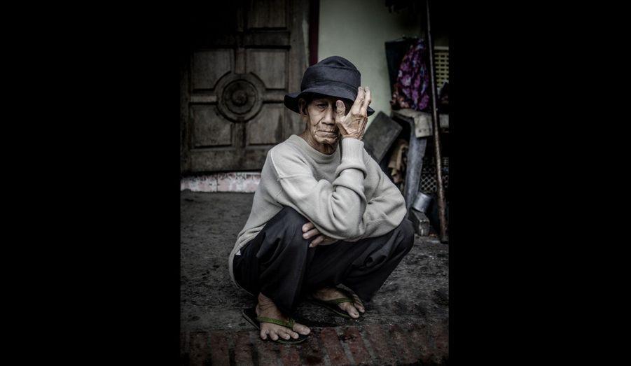 Un vieil homme se tient assis à Phnom Penh, au Cambodge.
