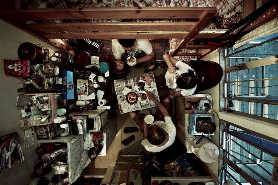 Difficile de se loger à Hongkong, 3e place financière au monde. Les plus pauvres vivent dans des « clapiers humains », minuscules box de moins de 10 mètres carrés. Ici, trois personnes à l'heure du dîner.