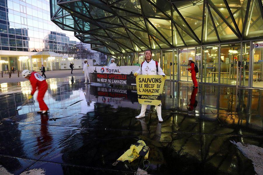 Des militants de Greenpeace ont déversé environ 3 000 litres de mélasse lundi matin devant le siège de Total à La Défense