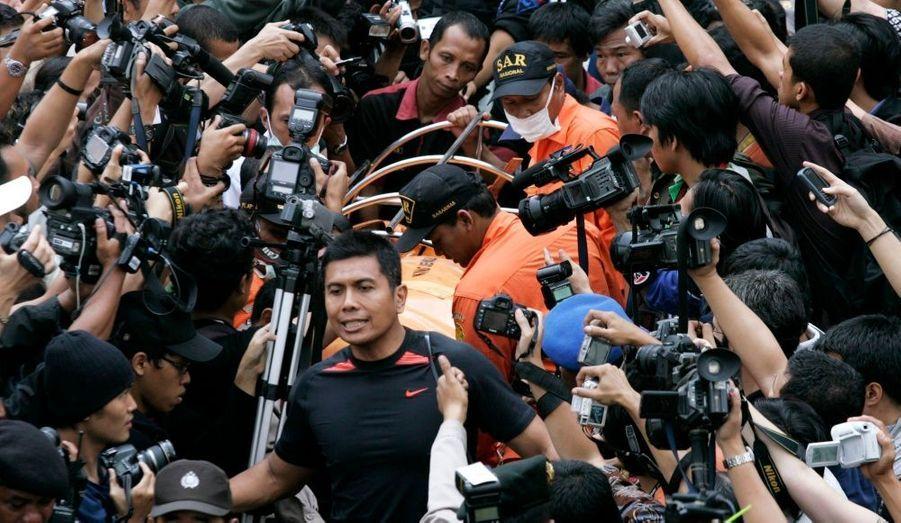 Des secouristes sont pris d'assaut par les photographes alors qu'ils transportent un corps.
