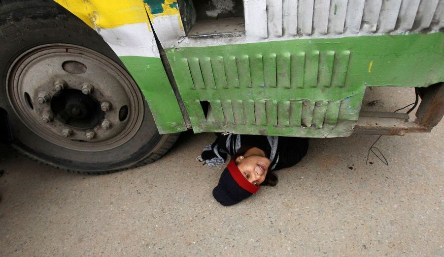 Un manifestant caché sous un bus
