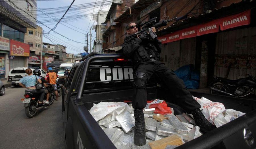 Un policier de l'antigang mène la garde sur le toit d'un pickup rempli de pains de marijuana. Les autorités de Rio de Janeiro ont mené un raid dans le bidonville de Rocinha, mardi. Trois tonnes de marijuana ont été saisies et sept personnes arrêtées.