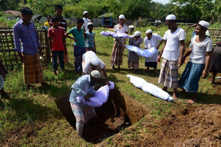 Des volontaires bangladais enterrent les corps des naufragés, le 9 octobre 2017.
