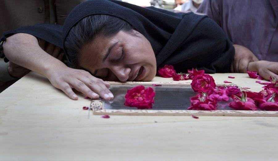 Une jeune femme pleure sur le cercueil de son frère à l'hôpital d'Islamabad, samedi.
