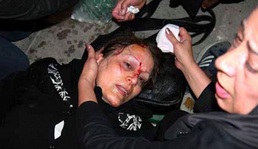 Une femme, gravement touchée, reçoit quelques soins.