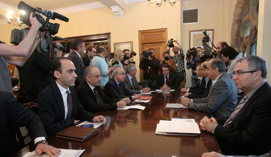 Le chef de l'État Nicos Anastasiades préside une réunion avec les chefs du parti et le gouverneur de la Banque centrale de Chypre au palais présidentiel de Nicosie. Après que le Parlement a rejeté massivement le plan sur les dépôts bancaires, les dirigeants cherchent à stabiliser les marchés financiers car les Chypriotes ont massivement retiré leurs épargnes des banques.