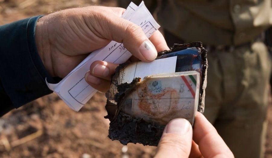 Un policier tient dans ses mains des papiers d'identités appartenant à l'un des passagers, retrouvés sur place après le crash.