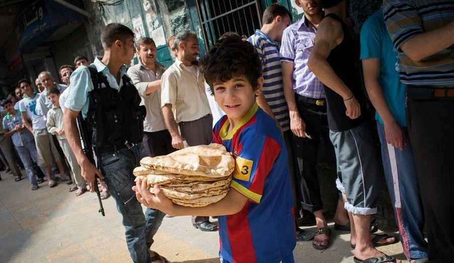 Le prix du pain a plus que doublé. Les files d'attente s'allongent devant les boulangeries, transformées en cibles prisées par l'armée. Un rebelle surveille pour éviter les pillages.