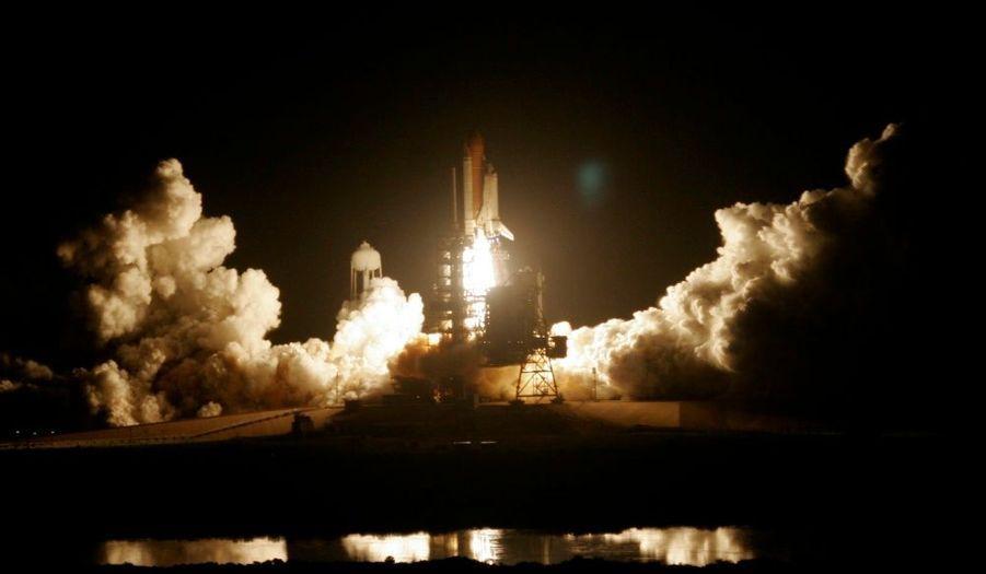 Discovery prend son envol de nuit au dessus de Cap Canaveral, provoquant un énorme nuage de fumée.