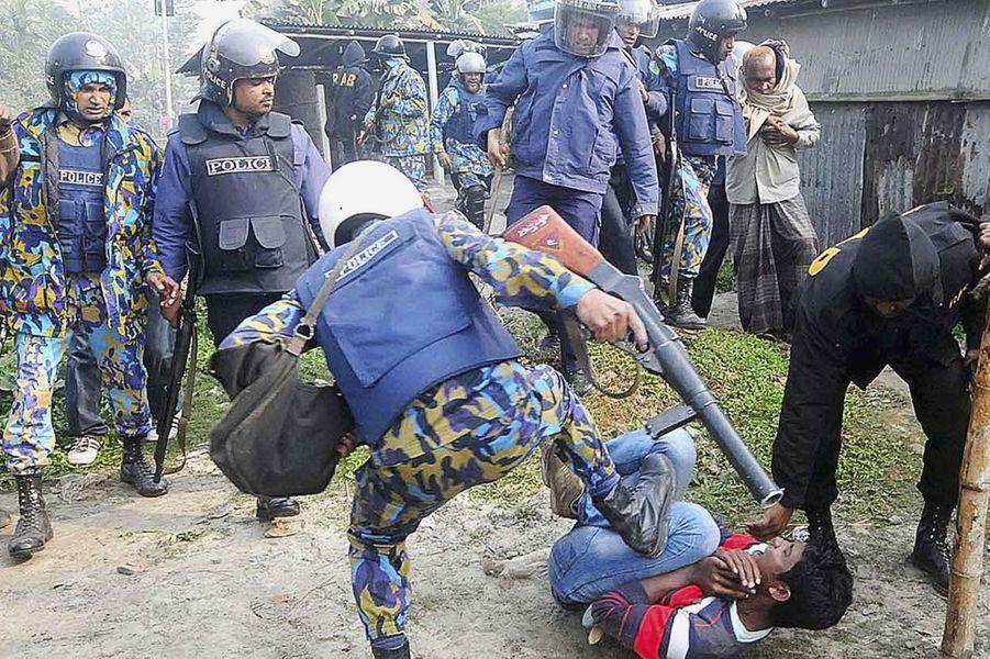 A Bogra, la police s'en prend à un manifestant après que plusieurs d'entre eux ont mis le feu à un bureau de vote.