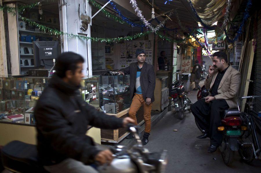 La journée, Waseem Akram (au centre), vend des accessoires pour téléphones. Le soir, il s'habille et vit comme une femme
