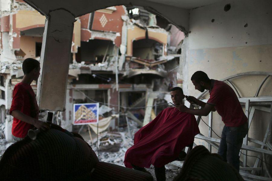 Un barbier rase un client dans les ruines de son ancien établissement, à Beit Hanoun