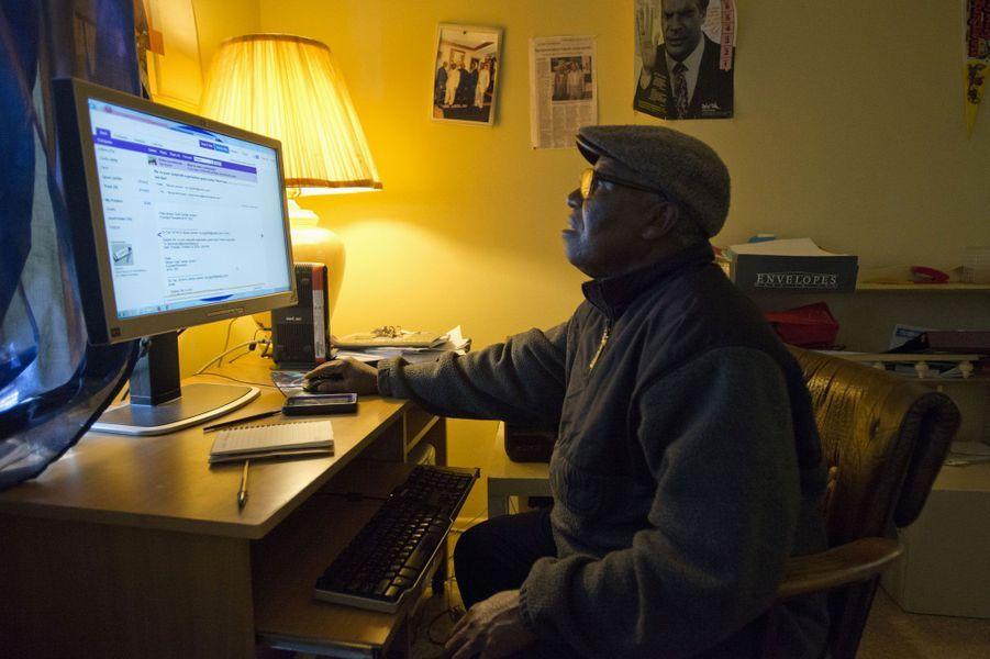 Moses Jensen, fondateur de l'organisation Immigrant Information Center, consulte ses mails