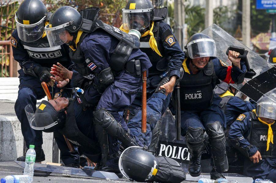 La «Mission Paix pour Bangkok» a mal tourné. Mardi, la police thaïlandaise a mené une vaste opération visant à reprendre le contrôle de sites de Bangkok, occupés depuis un mois par l'opposition qui réclame le départ de la Première ministre Yingluck Shinawatra. Bilan: un policier a été tué d'une balle dans la tête et 14 autres ont été blessés. Près de 15.000 policiers anti-émeutes ont été mobilisés, selon des sources sécuritaires. Des heurts ont éclaté près du siège du gouvernement, l'un des sites ciblés par les forces de l'ordre, envahi par des nuages de gaz lacrymogène. L'objectif était de débloquer l'accès aux principaux bâtiments officiels du centre et du nord de la capitale thaïlandaise. Selon la police, une centaine d'opposants ont été arrêtés près du ministère de l'Energie, un des sites repris parmi les cinq sites visés.