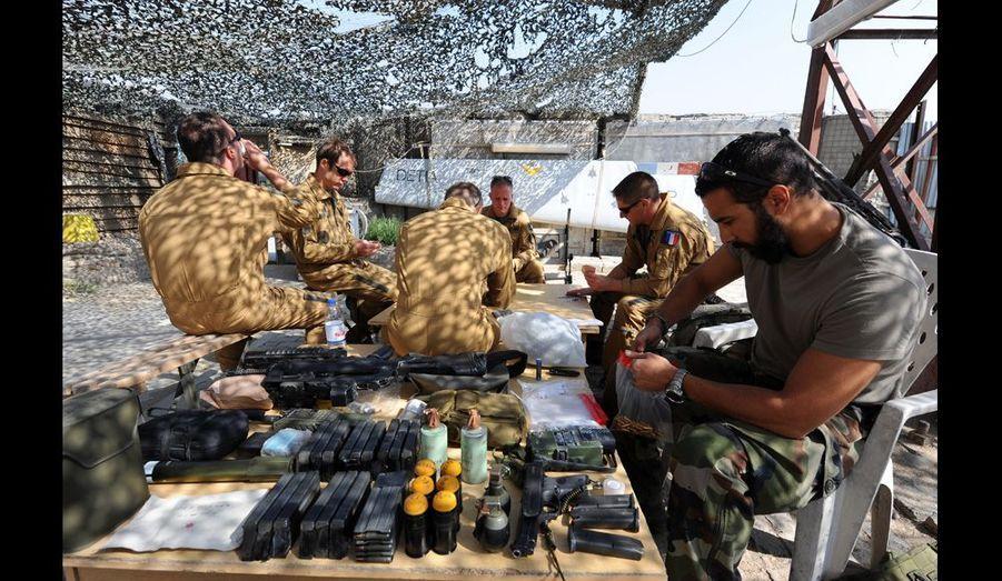 Des armuriers préparent soigneusement les bandes d'obus et de roquettes qui seront embarqués à bord des appareils.