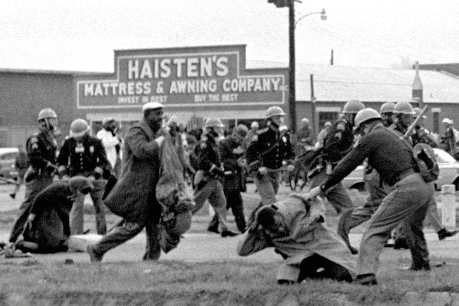 """Ci-dessus, la violente répression du """"Bloody Sunday"""" le 7 mars 1965.Par AFP. """"Le travail n'est pas terminé"""": Barack Obama célèbre samedi à Selma (Alabama) la marche pour les droits civiques qui a marqué un tournant dans l'histoire des Etats-Unis en garantissant le droit de vote aux Afro-Américains des Etats du Sud.Le premier président noir de l'histoire des Etats-Unis doit s'exprimer devant le pont Edmund Pettus sur lequel, le 7 mars 1965, plusieurs centaines de manifestants pacifiques furent violemment repoussés par la police dans un assaut qui traumatisa l'Amérique et aboutit, quelques mois plus tard, au Voting Rights Act.Barack Obama avait trois ans au moment des faits. Il a appris cette histoire par sa mère, quand il avait """"six, sept, huit ans"""". """"Elle me donnait des tas de livres pour enfants sur la lutte pour les droits civiques. Elle mettait des chansons de Mahalia Jackson (qui fut une proche de Martin Luther King, NDLR)"""", a-t-il raconté à la veille de cette célébration.Le discours présidentiel intervient trois jours après la publication d'un rapport accablant du ministère de la Justice pointant les comportements discriminatoires de la police de Ferguson (Missouri), théâtre de violentes émeutes après la mort en août dernier d'un jeune Noir abattu par un policier blanc.Selma, ville de 20.000 habitants (dont 80% de Noirs), se prépare depuis plusieurs jours à ce week-end de commémoration auquel l'ancien président George W. Bush et plus d'une centaine d'élus du Congrès doivent participer.Le 15e amendement de la Constitution américaine, adopté en 1870, interdit de refuser le droit de vote à tout citoyen """"sur la base de sa race ou de sa couleur"""". Dans plusieurs Etats du Sud, il a longtemps été bafoué.""""Au rythme actuel, il faudra 103 ans pour que les 15.000 Noirs du comté de Dallas puissent s""""inscrire sur les listes électorales"""", lançait Martin Luther King en janvier 1965 à Selma.Si la loi signée le 6 août 1965 par le président Lyndon Johnson a marqué une rupture, no"""