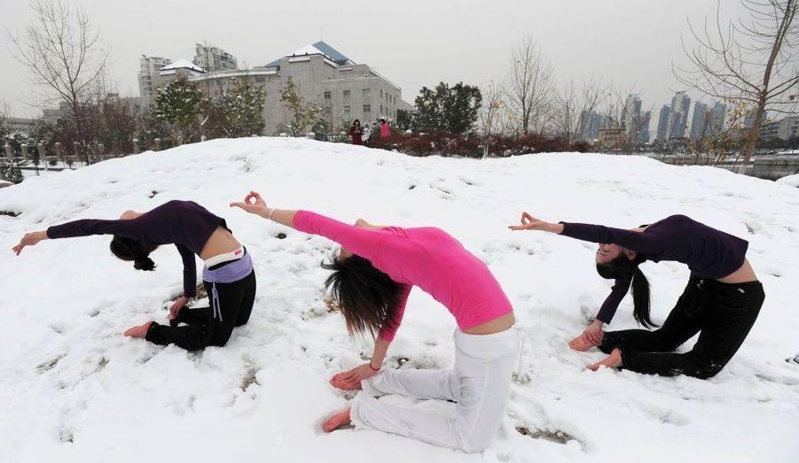 Trois jeunes femmes pratiquent le yoga en plein air malgré le froid et la neige à Shangaï.