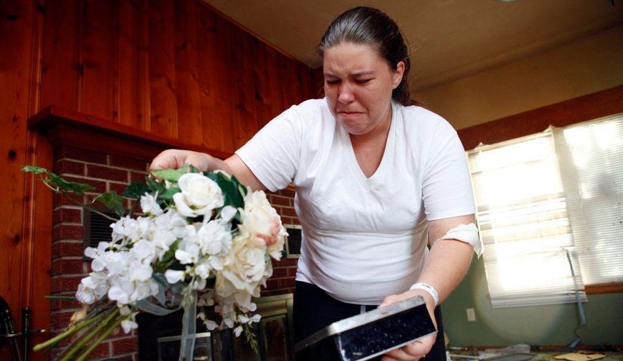 Une femme en pleurs, après avoir retrouvé son bouquet de mariée dans les ruines de sa maison.