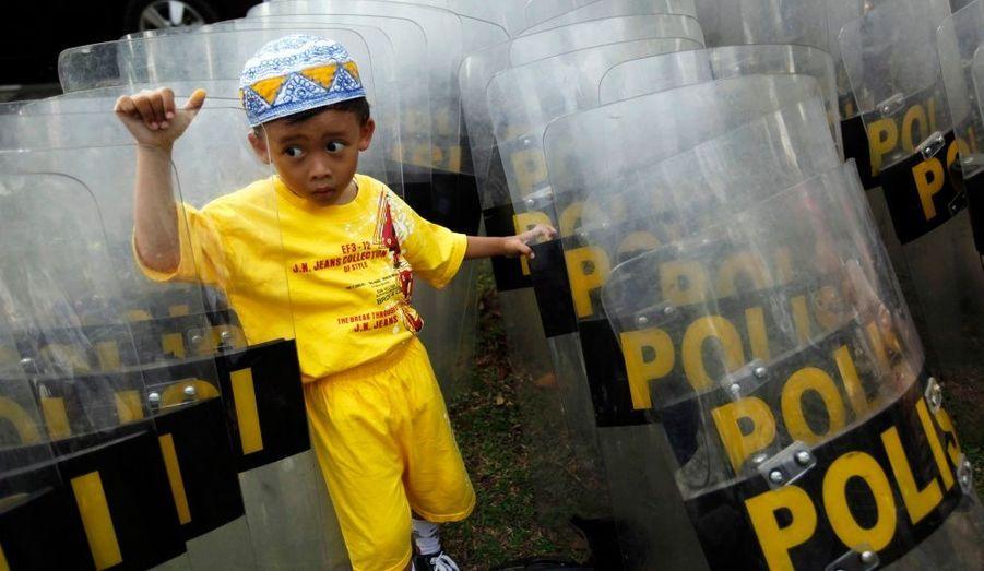 Un petit garçon indonésien se réfugie derrière des boucliers de police pendant que sa mère participe à une manifestation anti-Israël à l'ambassade américaine de Jakarta.