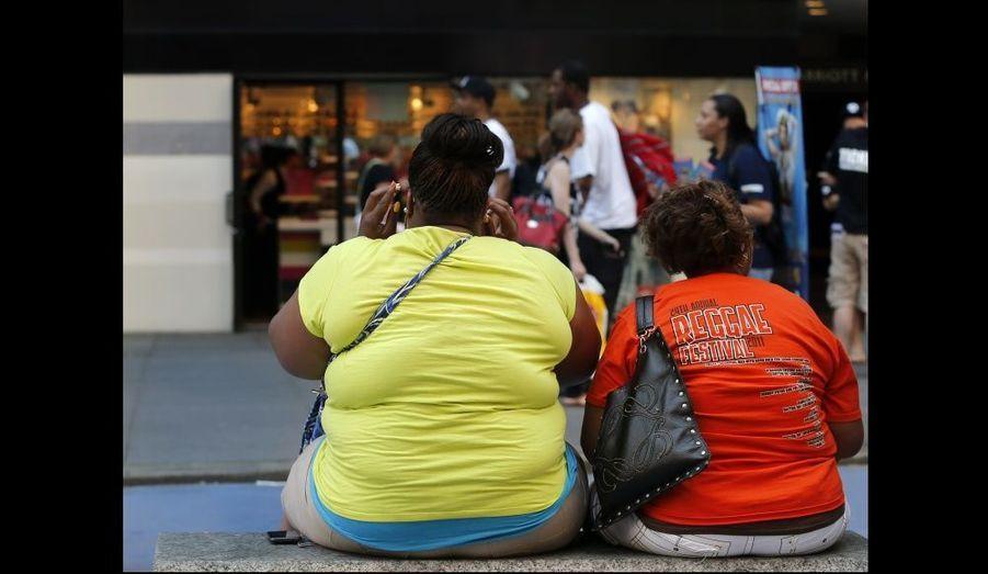 Deux femmes assises attendent sur Times Square, à New York.